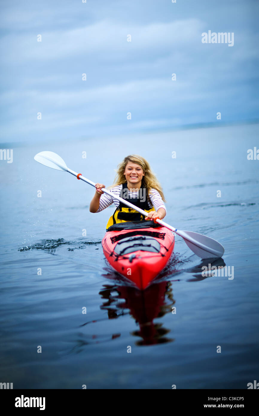 Woman rowing canoe on lake, smiling Photo Stock