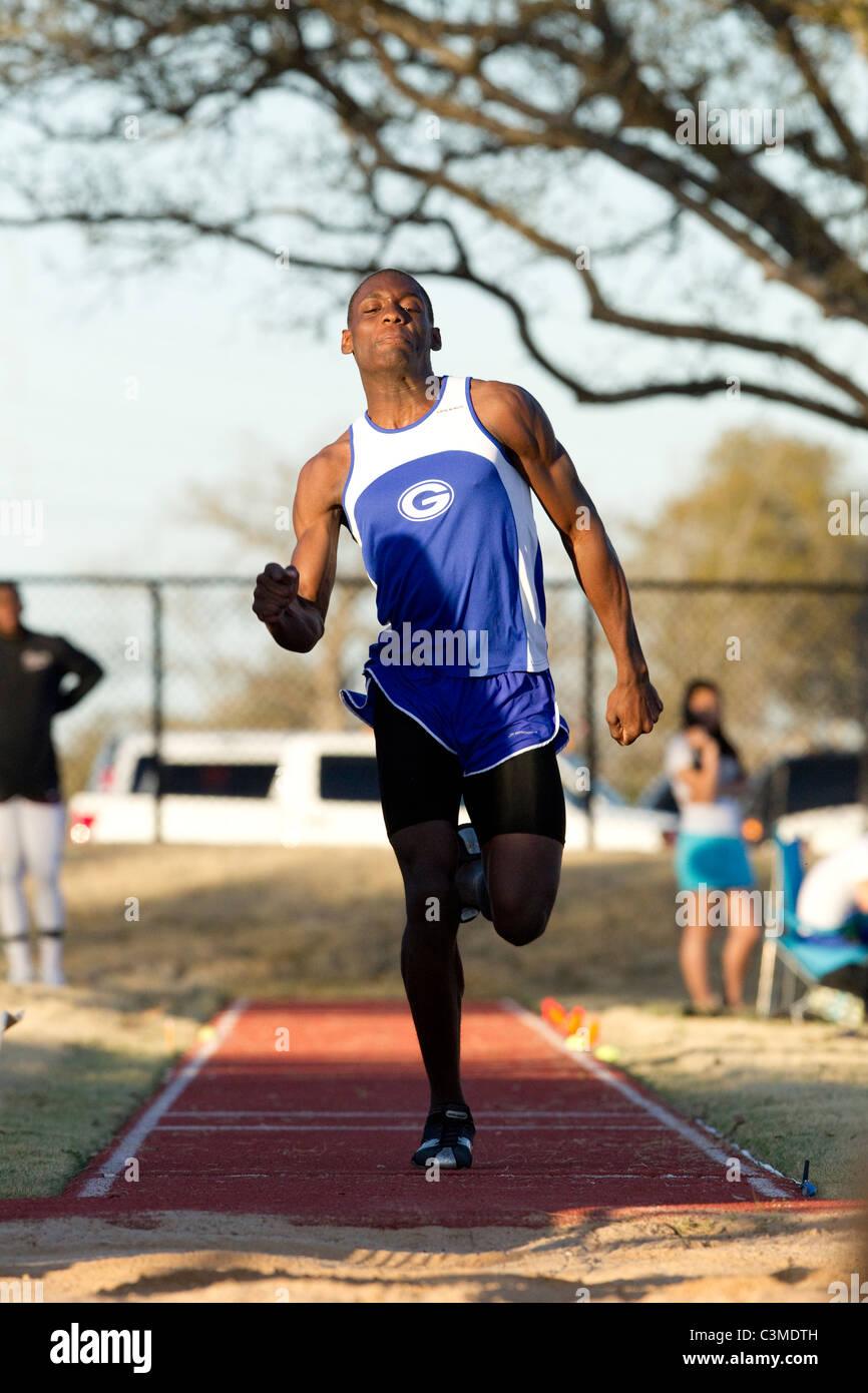 Athlète afro-américain dans le décollage des approches au saut en longueur de voie de lycée Photo Stock