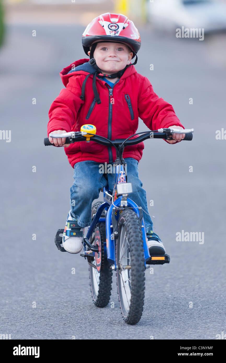Un garçon de trois ans équitation son vélo le premier jour sans stabilisateurs dans l'Uk Banque D'Images