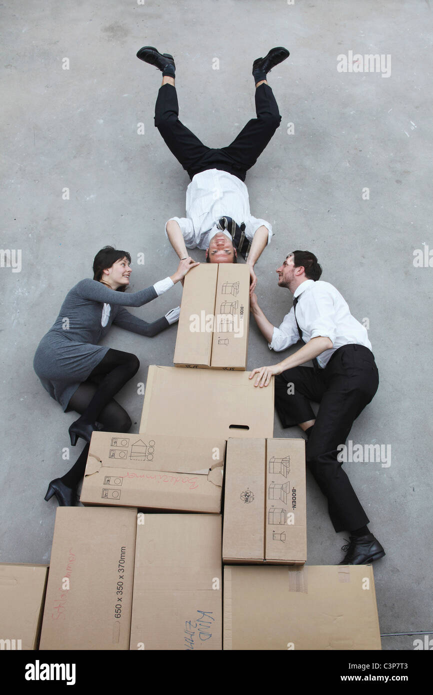 Trois personnes sur des boîtes en carton, man doing handstand, smiling, portrait, elevated view Photo Stock
