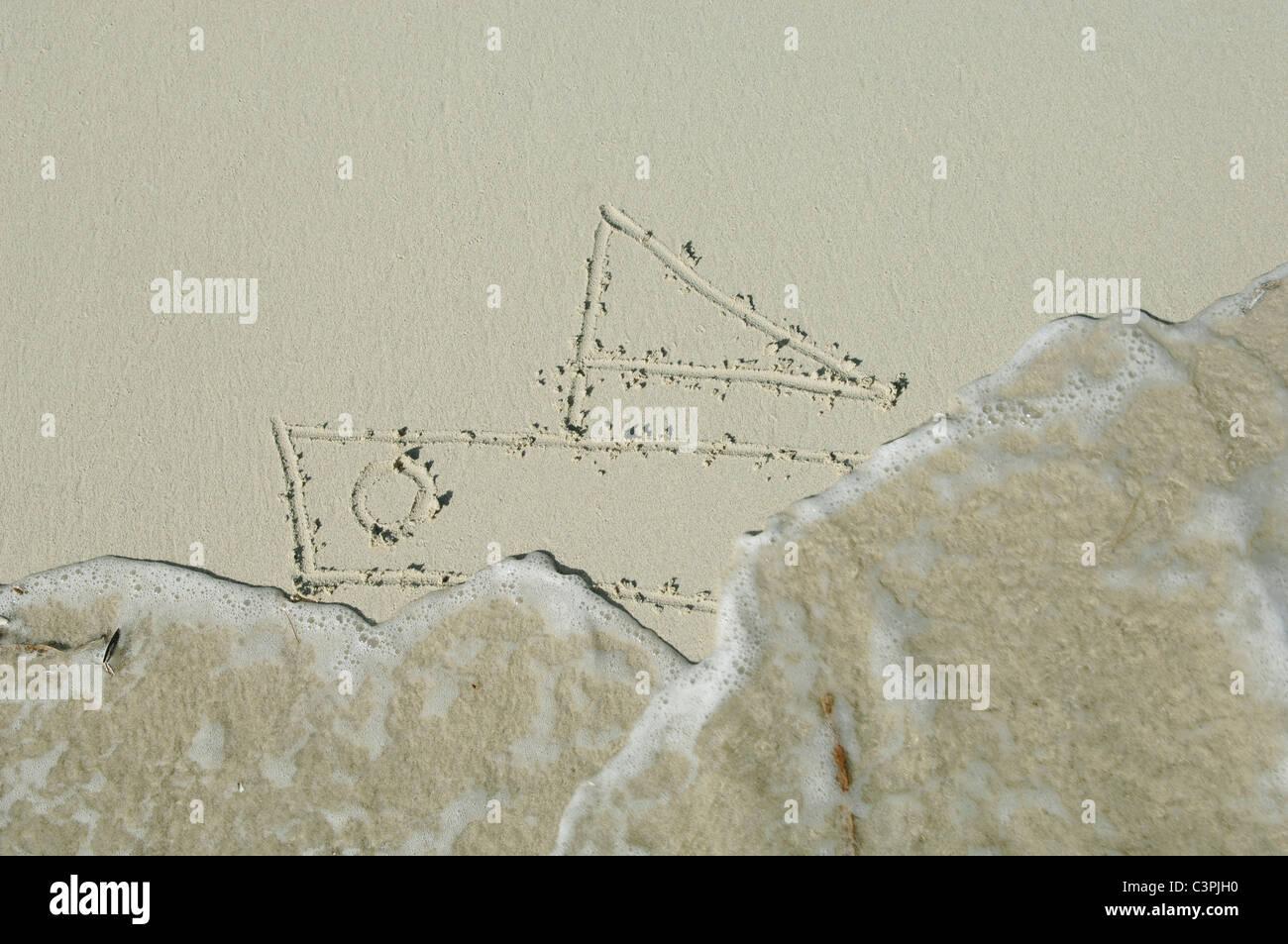 Navire dessiné dans le sable sur la plage par la mer. Photo Stock