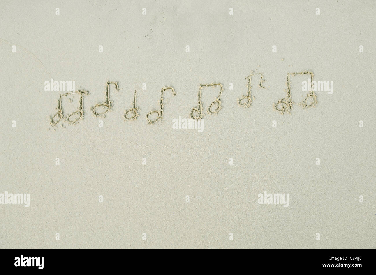 Des notes de musique dessiné dans le sable sur la plage. Photo Stock