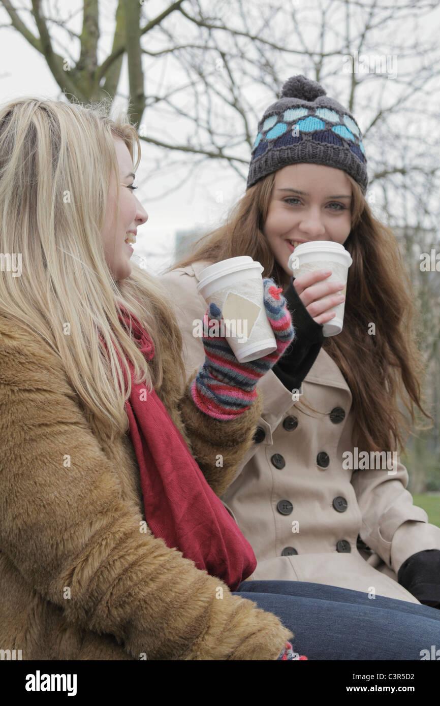 2 jeunes femmes avec des tasses à emporter Photo Stock