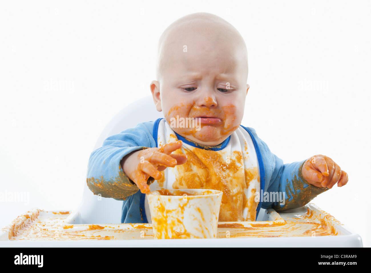 Baby Boy (6- 11 mois) avec des aliments pour bébé et de pleurer Photo Stock