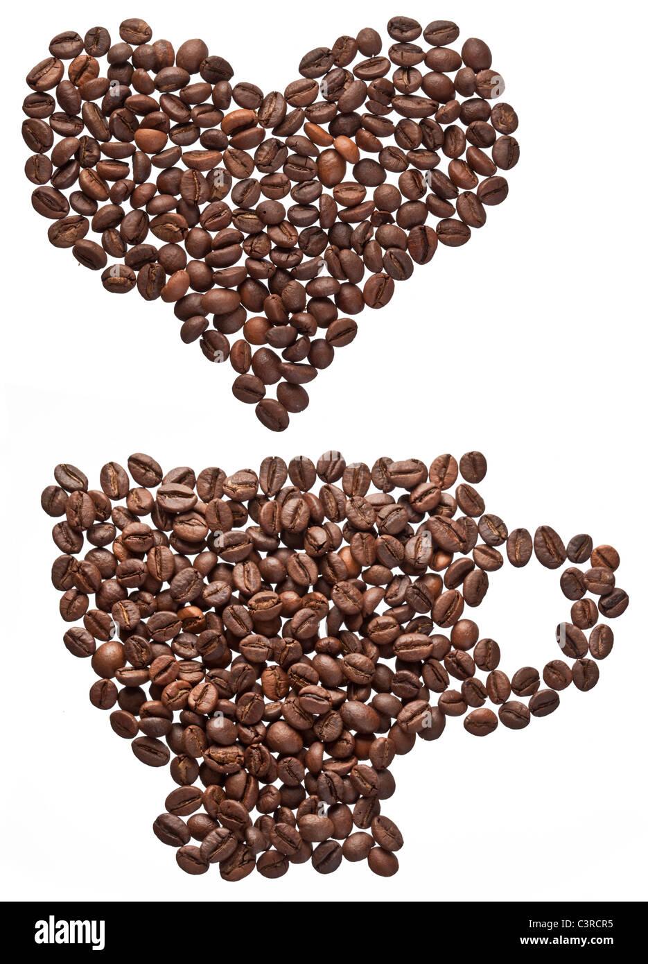 Café en grains en forme de coeur et tasse isolé sur fond blanc. Photo Stock
