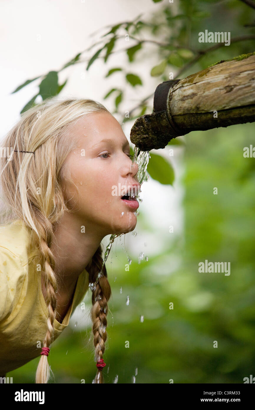 L'Autriche, Mondsee, Girl (12-13 ans) l'eau potable de la tuyère d'eau Photo Stock
