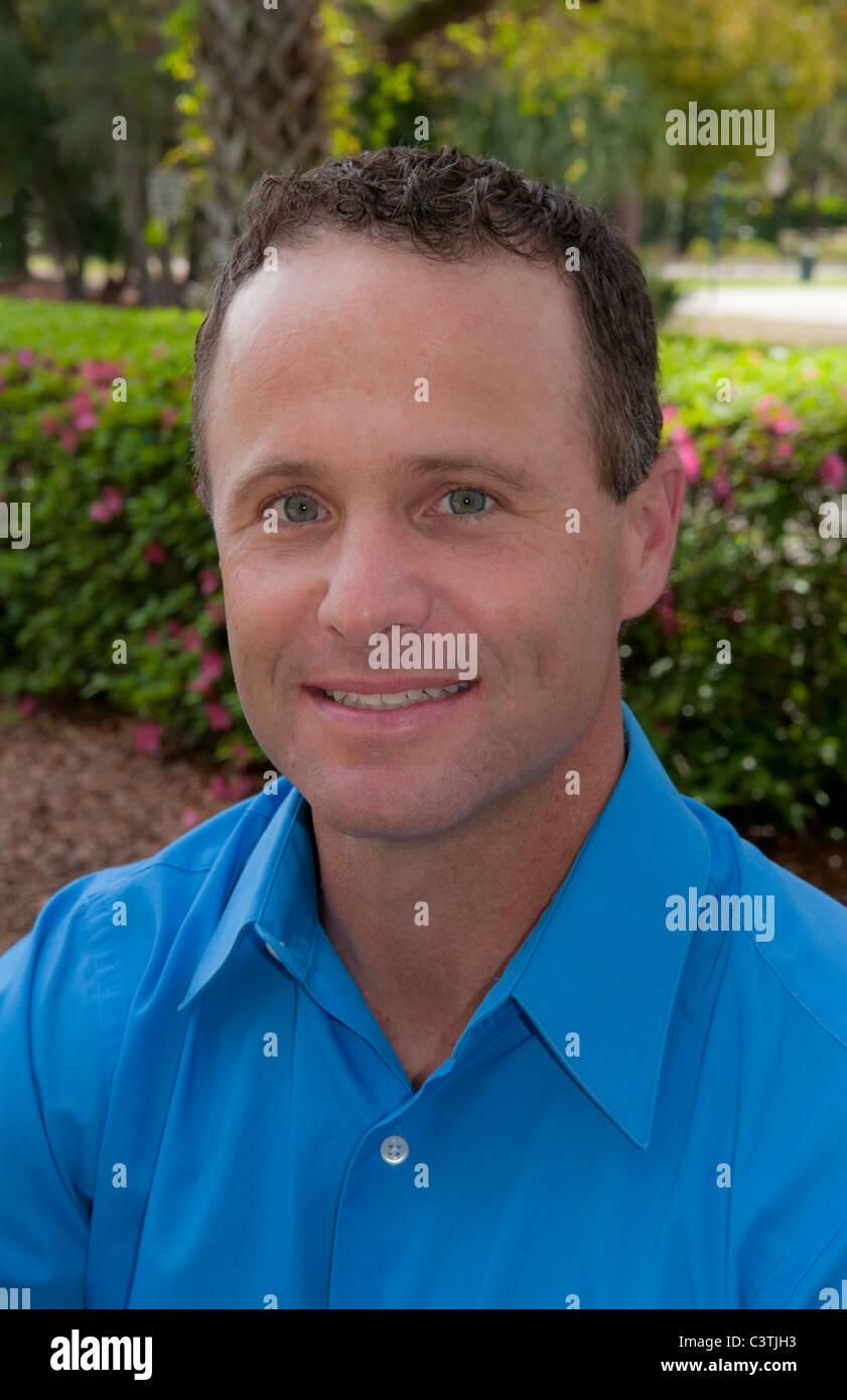 Portrait d'homme âgé de 30 ans à l'extérieur en parc avec chemise bleue Photo Stock