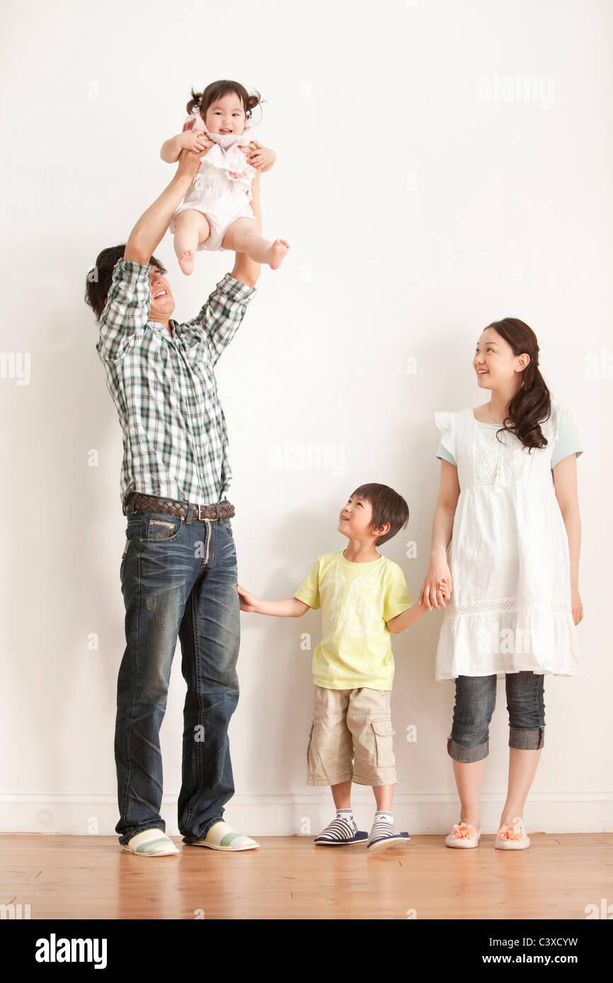 La mère et le Fils Père regardant bébé fille de levage Banque D'Images