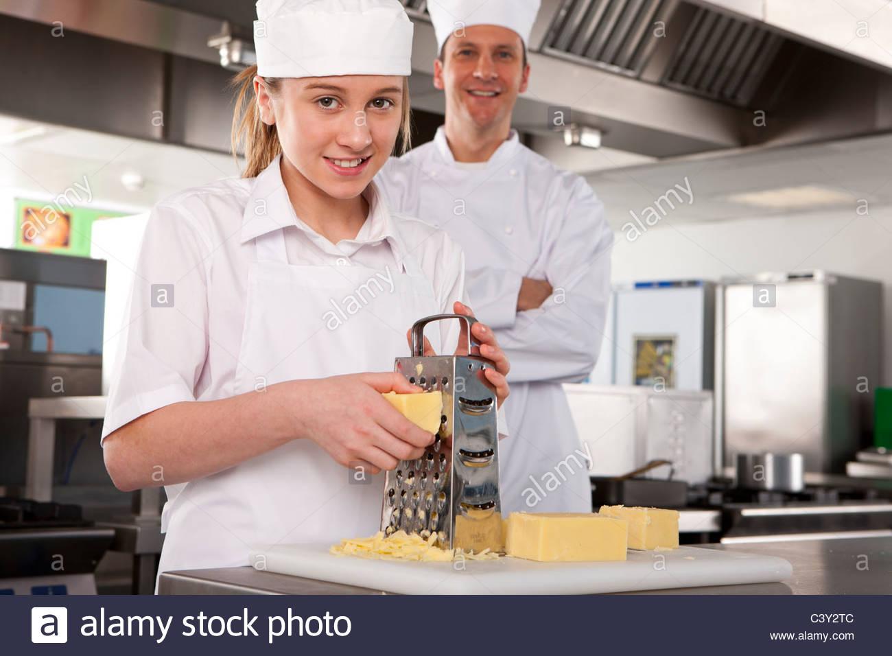 Regarder Chef fromage râper stagiaire en cuisine commerciale Photo Stock