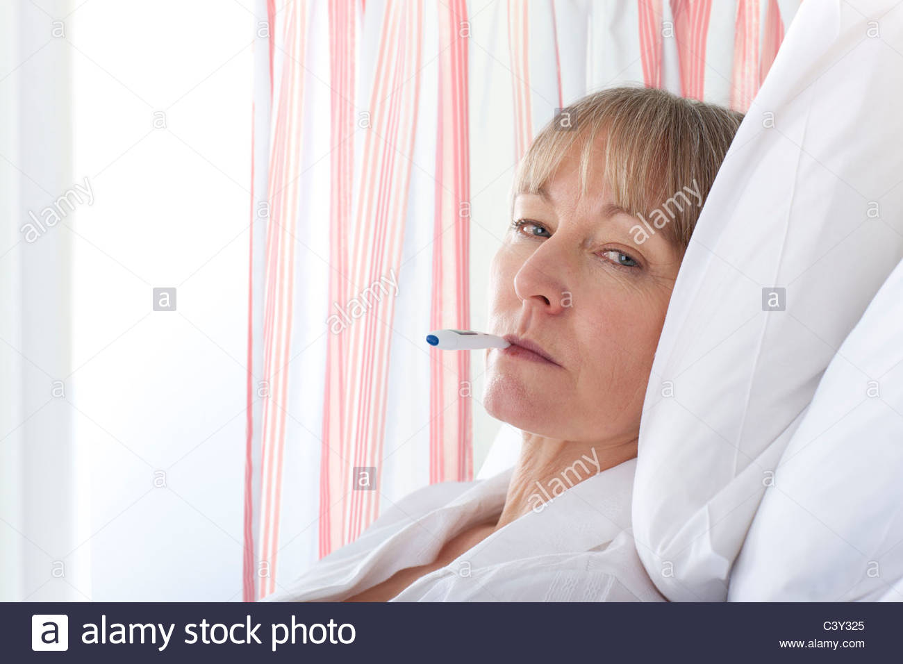 Après avoir pris la température du patient in hospital room Photo Stock