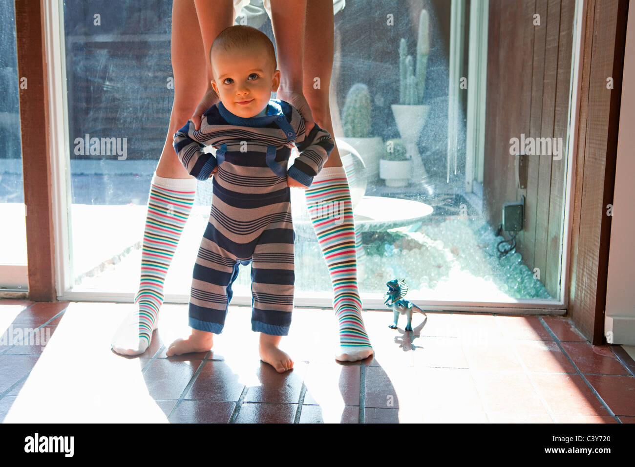Mother helping baby son prendre Premiers pas Photo Stock