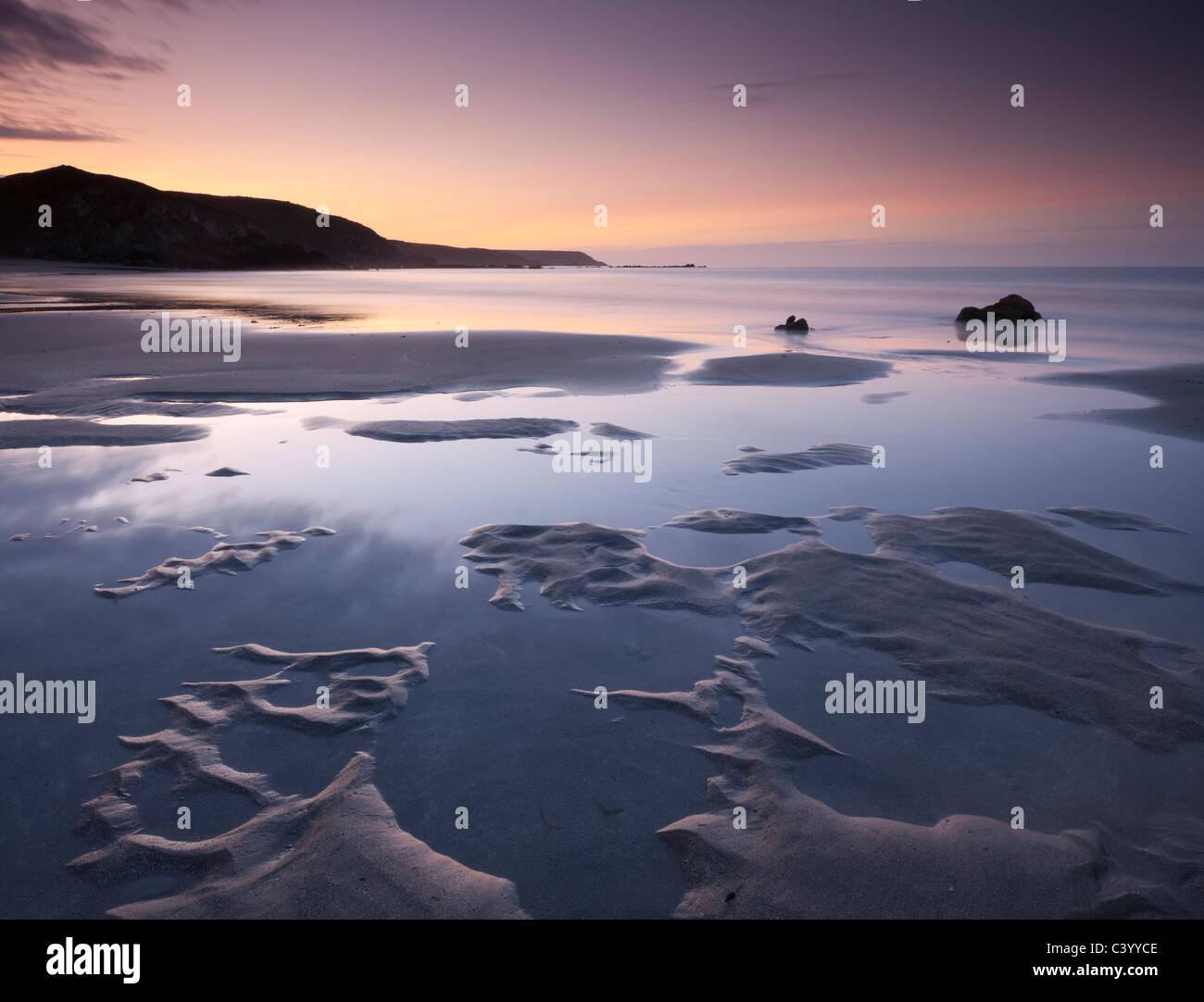 Les piscines de l'eau sur la plage de sable de Kennack Sands au lever du soleil, Péninsule du Lézard, Photo Stock
