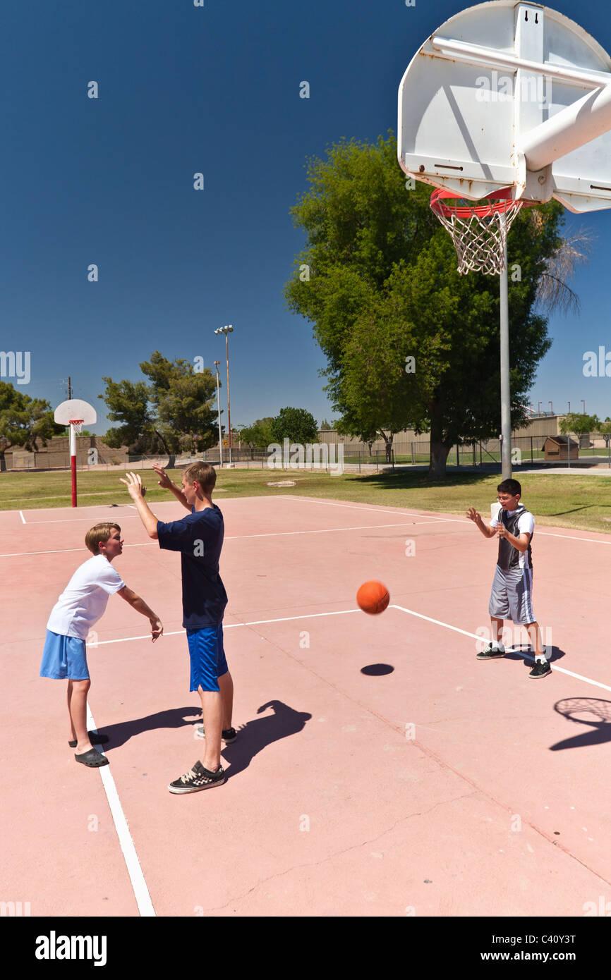 Garçons jouant au basket-ball à un parc de quartier en plein air Photo Stock