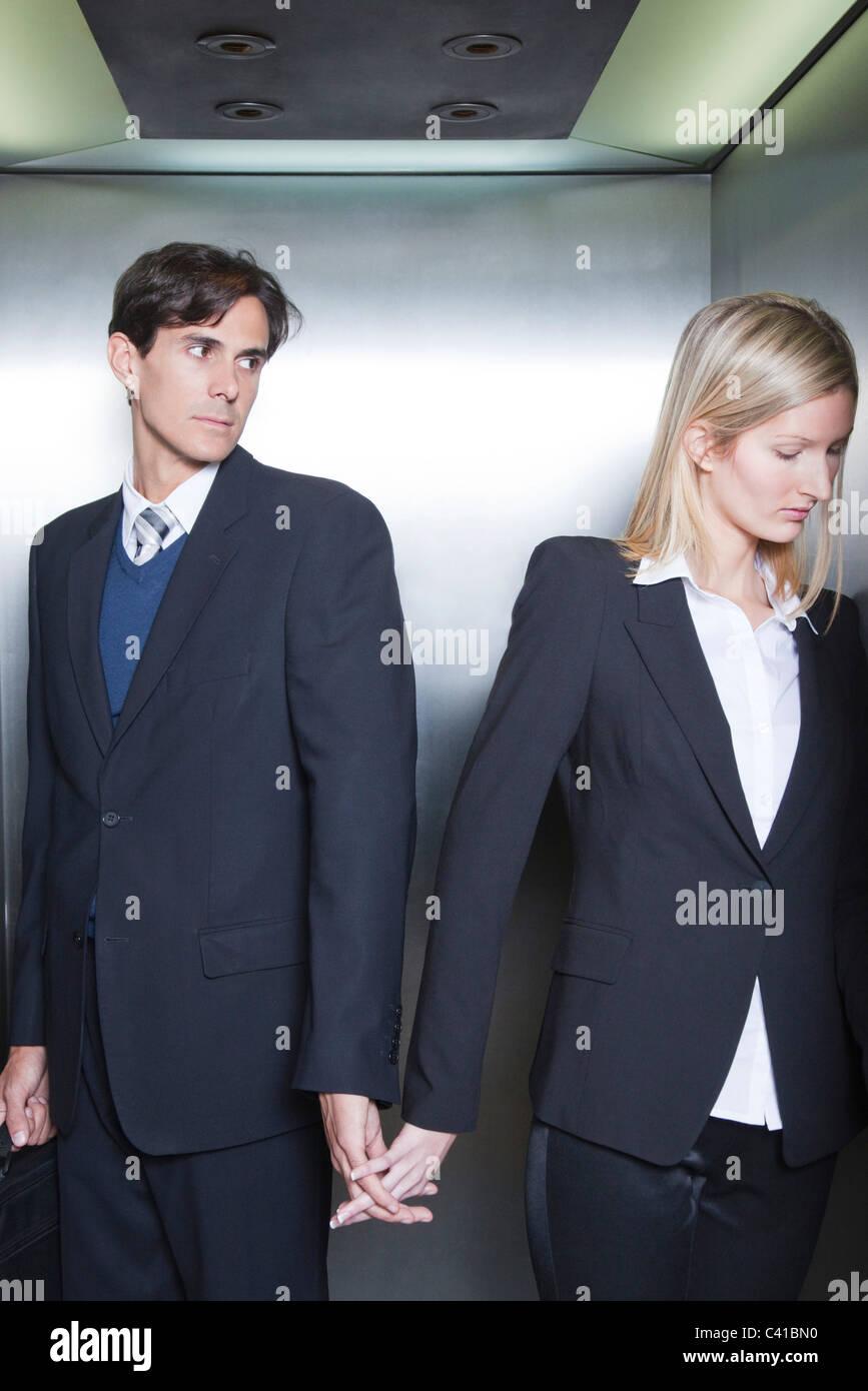 Couple habillé en tenue de tenir la main dans l'élévateur Banque D'Images