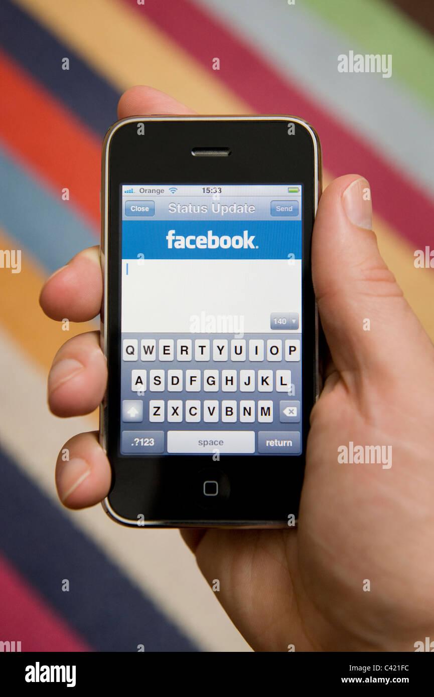 Close up of male hand holding un iPhone sur le point de mettre à jour son statut Facebook. (Usage éditorial Photo Stock