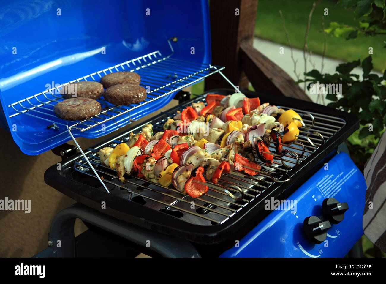 Un barbecue avec des légumes sur les brochettes et les burgers Photo Stock