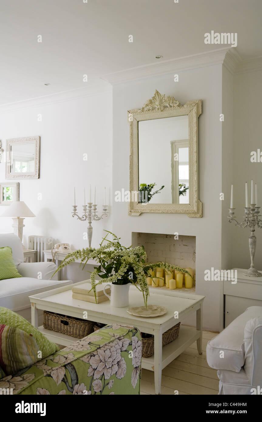 White salon avec table basse, miroir et un canapé à motifs floral. Photo Stock