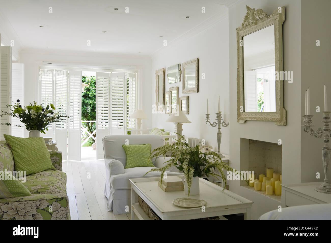 White salle de séjour avec cheminée, miroir, arrangements de fleurs et de fauteuils Photo Stock