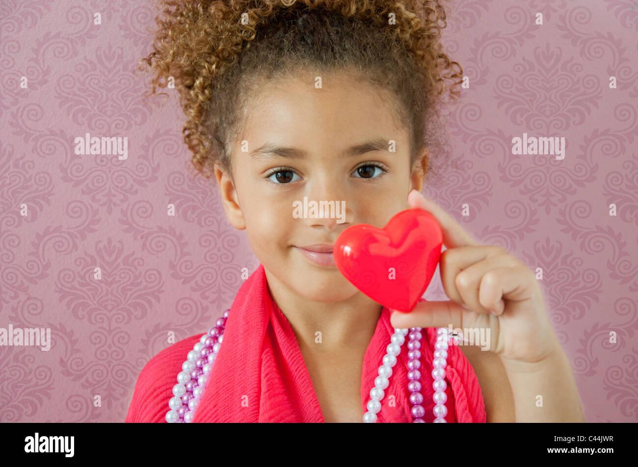 Jeune fille tenant un cœur dans une chambre rose Photo Stock