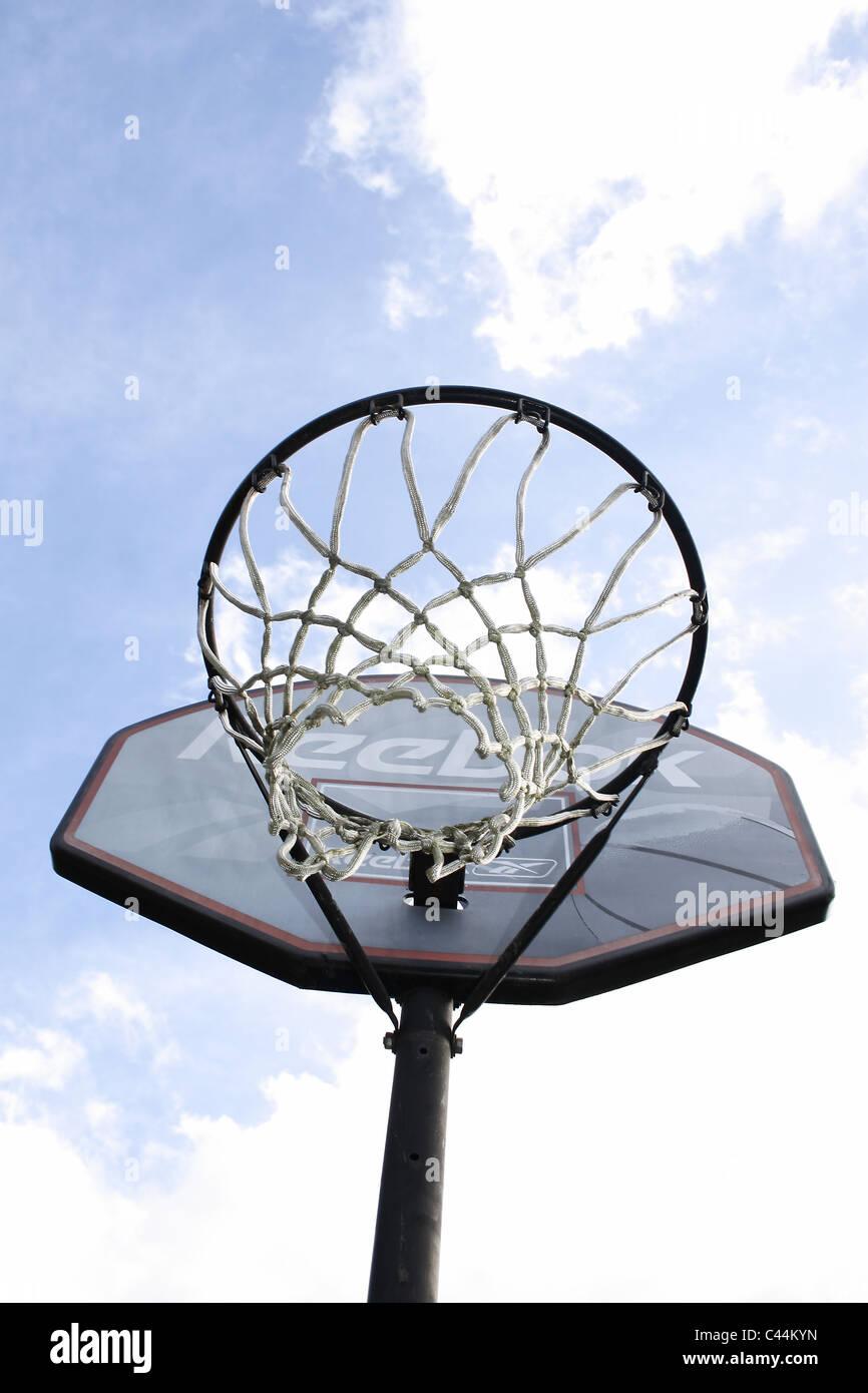 Basket-ball reebok contre net ciel nuageux Photo Stock