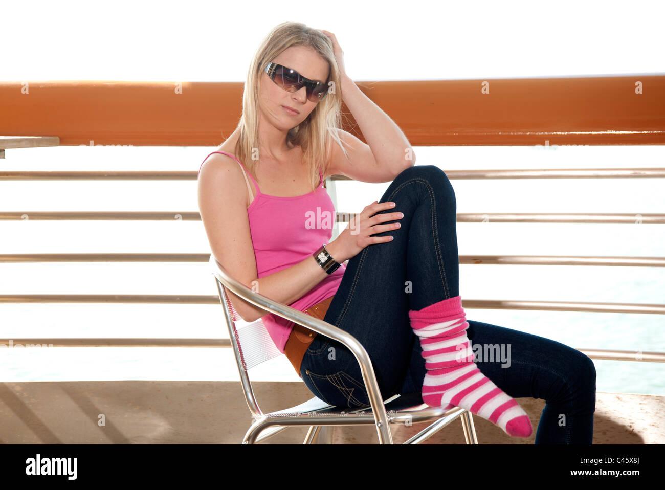 jeune femme assise sur une chaise avec une debout portant des lunettes de soleil sur le. Black Bedroom Furniture Sets. Home Design Ideas