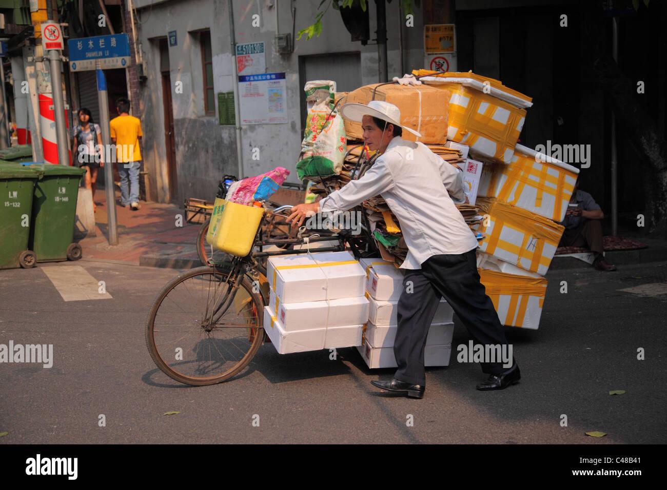 Homme pousse surchargé location, Guangzhou, Chine Banque D'Images