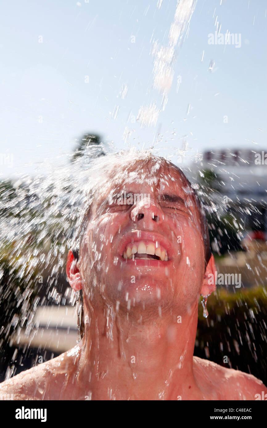 Parution du modèle homme sur des vacances lave ses cheveux sous la douche avec les projections d'eau. Photo Stock