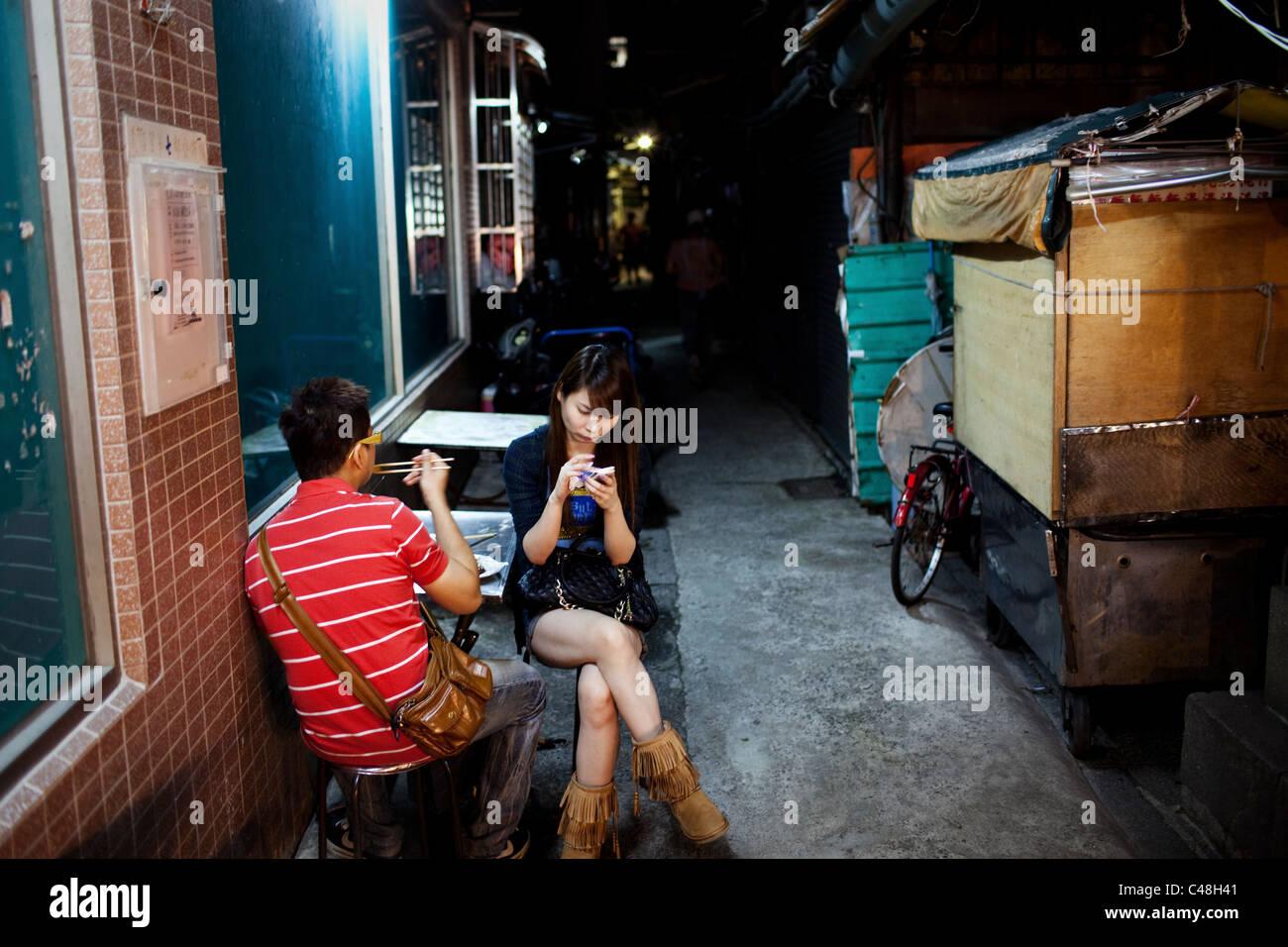 Tout en mangeant avec son petit ami, une adolescente de textes dans une allée au marché de nuit de Shilin, Photo Stock
