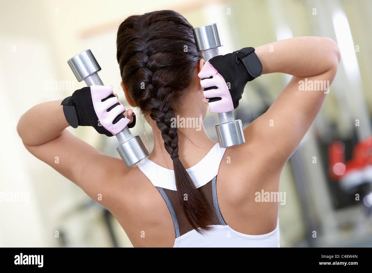 Vue arrière des jeunes filles faisant des exercices avec haltères in gym Photo Stock