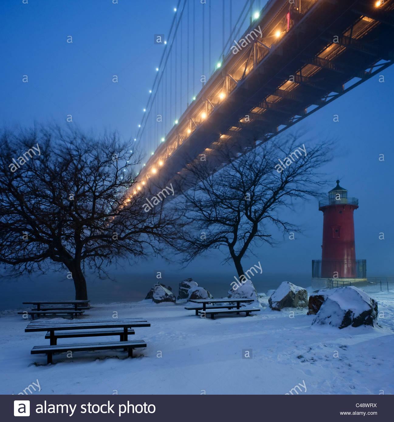 Un petit phare rouge est assis sous un grand pont dans la neige au crépuscule. Photo Stock