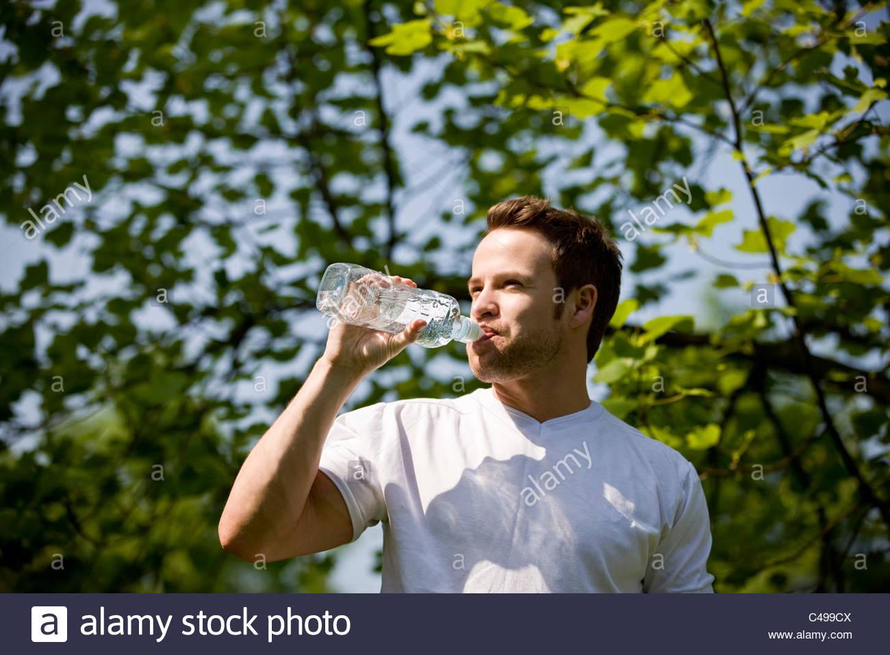 Un jeune homme d'une bouteille d'eau potable Photo Stock