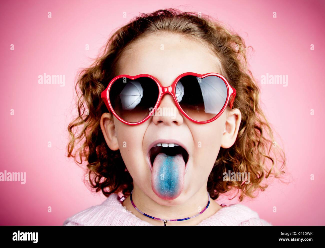 une jeune fille aux cheveux boucl s sur un mur de studio rose portant des lunettes de soleil en. Black Bedroom Furniture Sets. Home Design Ideas