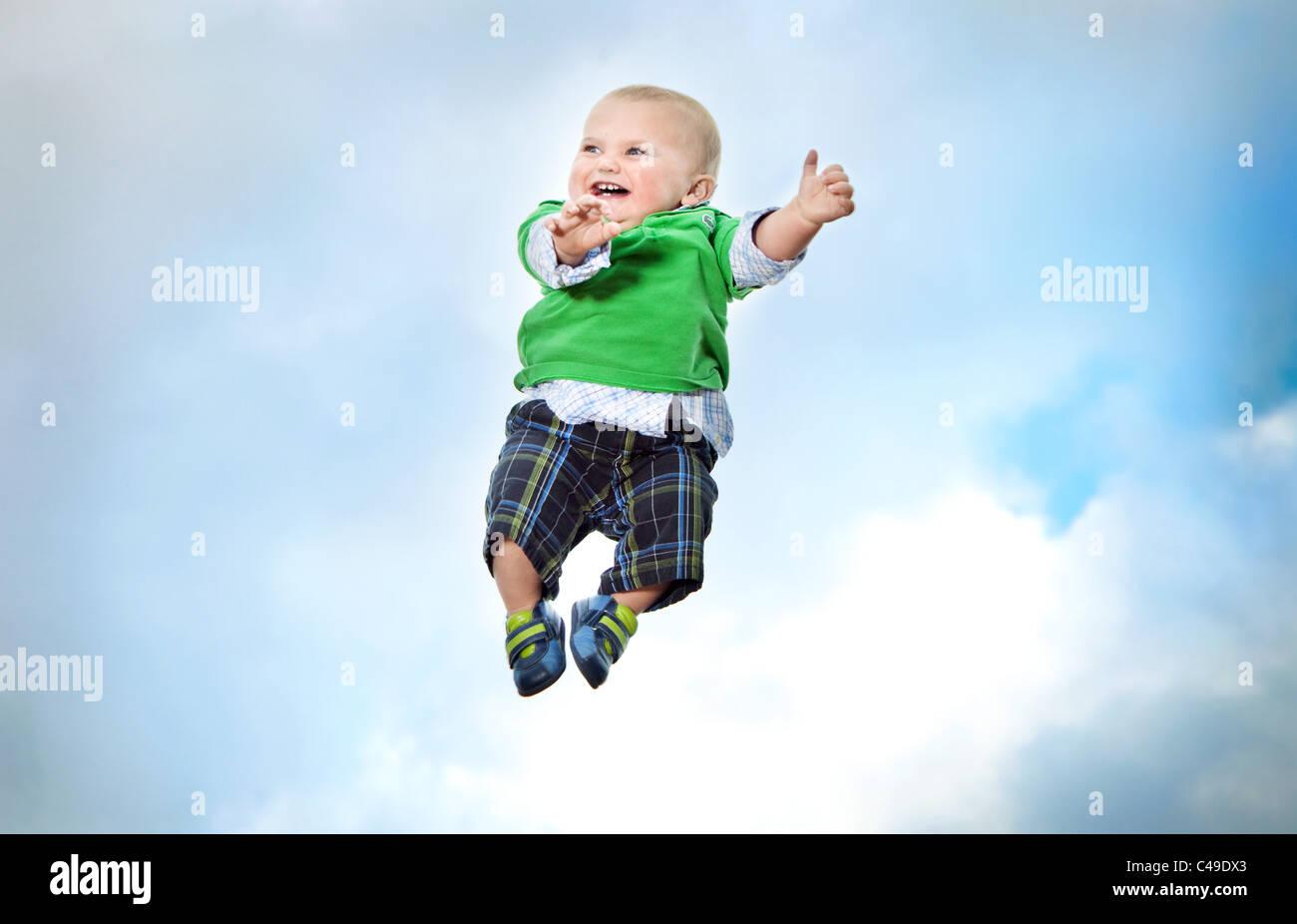 Un petit garçon dans des vêtements volant dans les airs contre un ciel bleu. Photo Stock