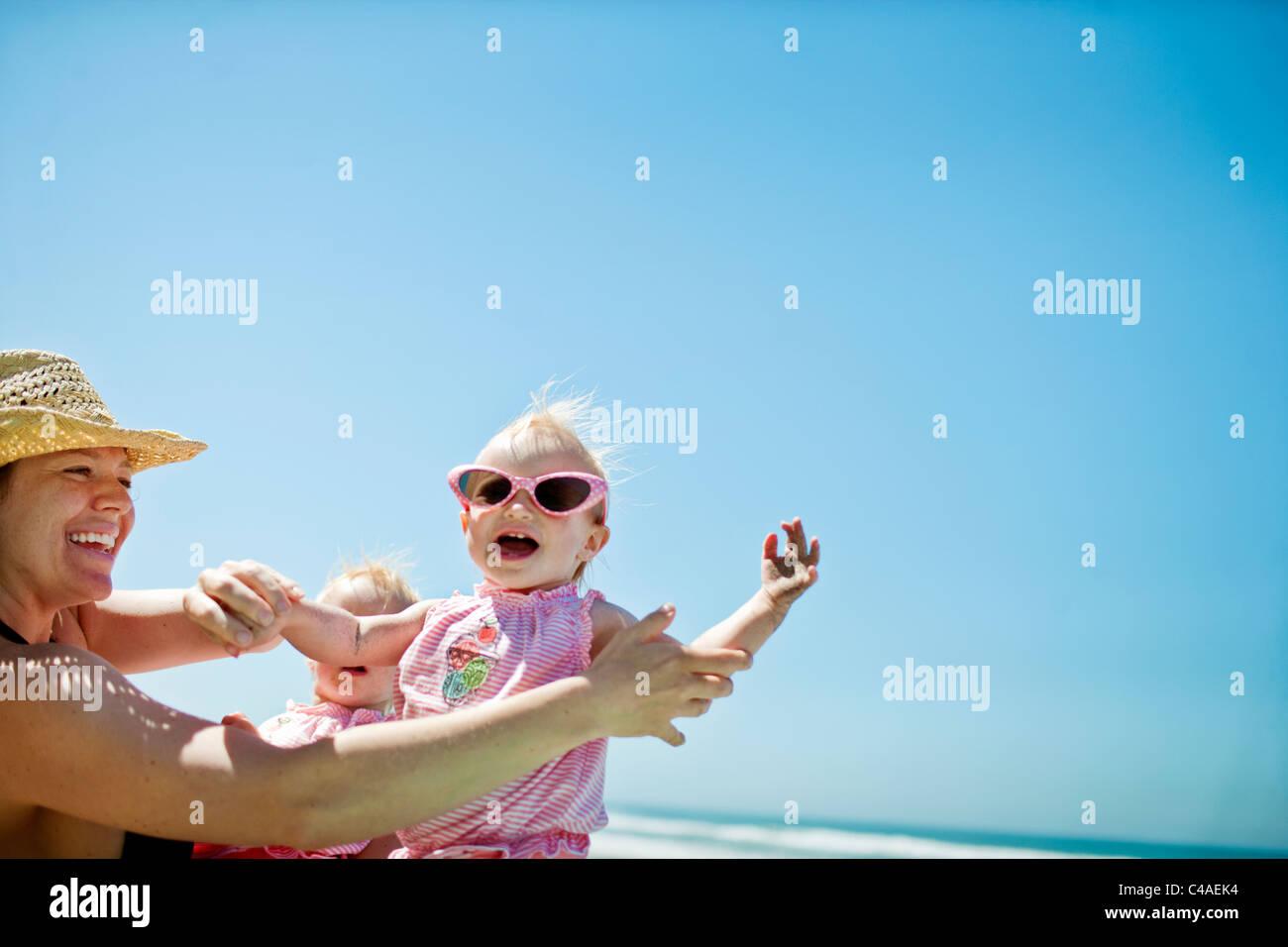 Mère jouant avec sa fille sur la plage Photo Stock
