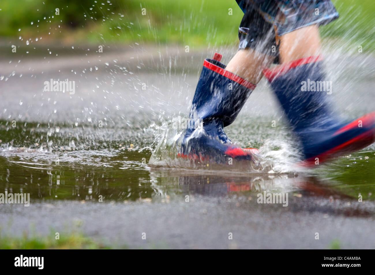 Bottes de pluie s'éclabousser dans une flaque Banque D'Images