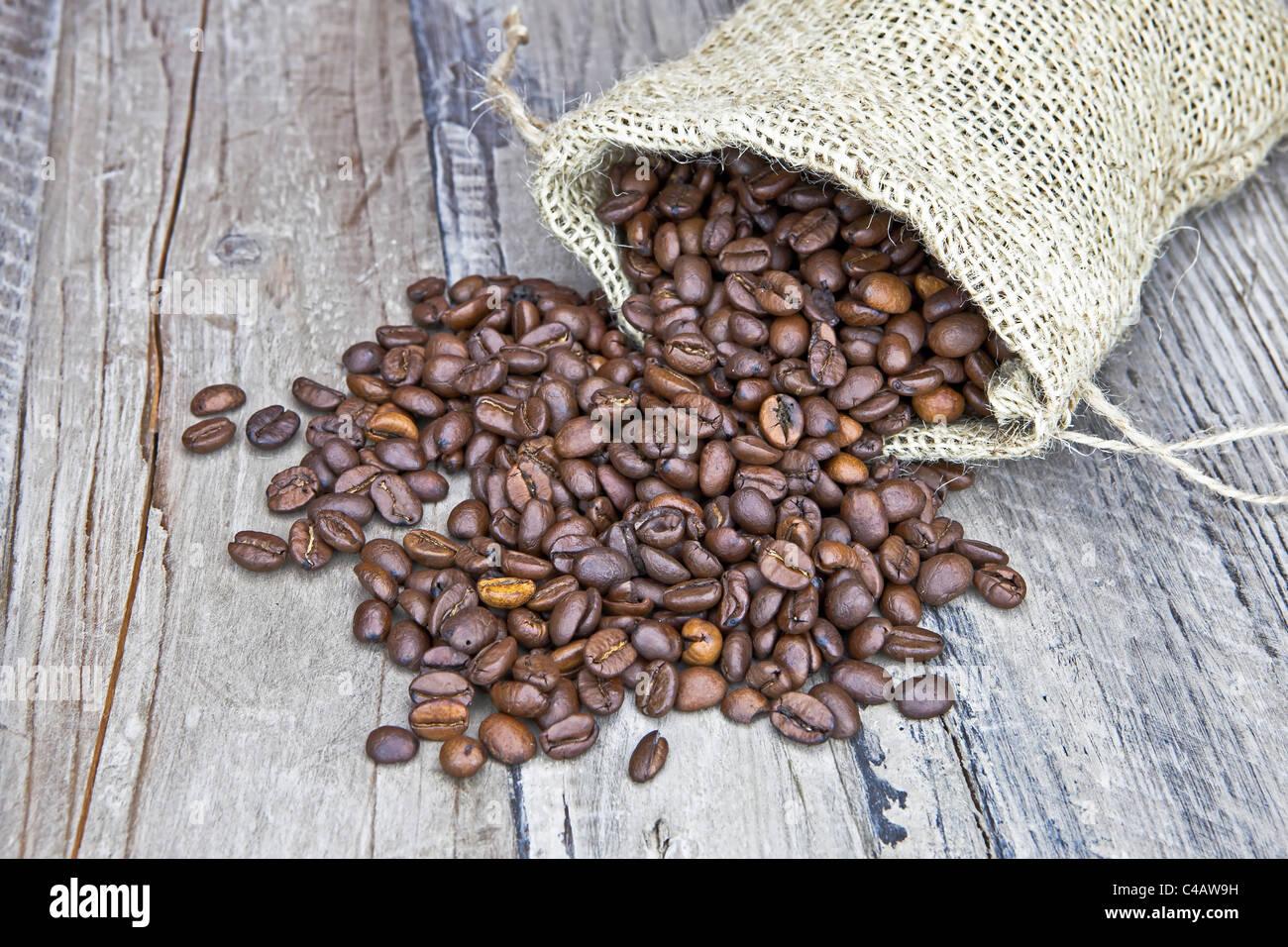 Grains de café dans un sac de jute sur une table en bois Photo Stock