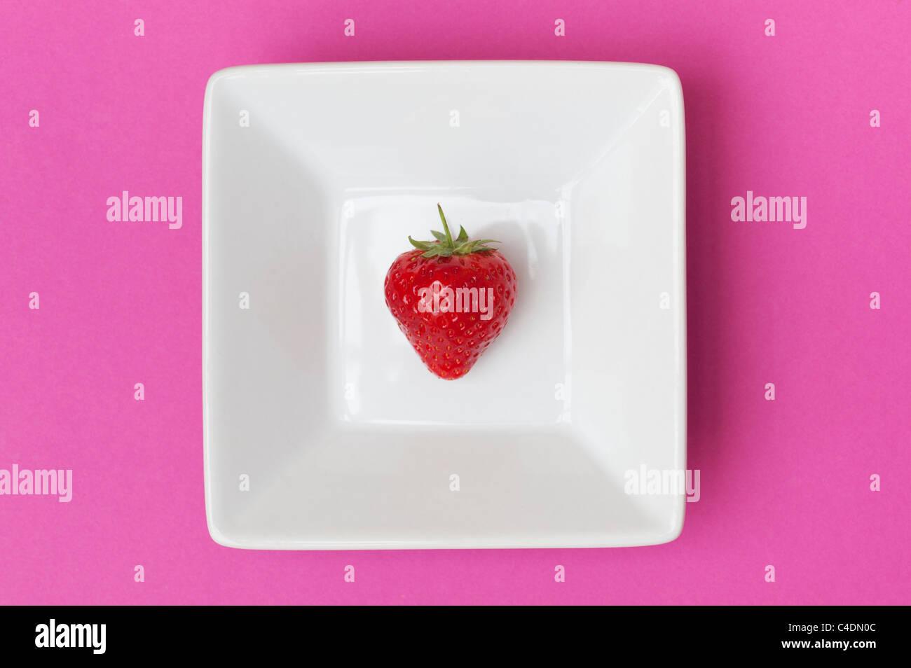 Fraise dans un carré plat de céramique sur fond rose Photo Stock
