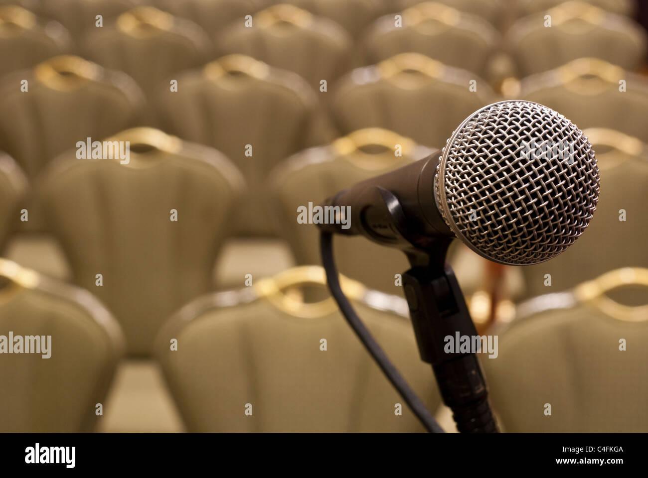 Microphone devant plusieurs rangées de chaises vides avec une faible profondeur de champ Photo Stock
