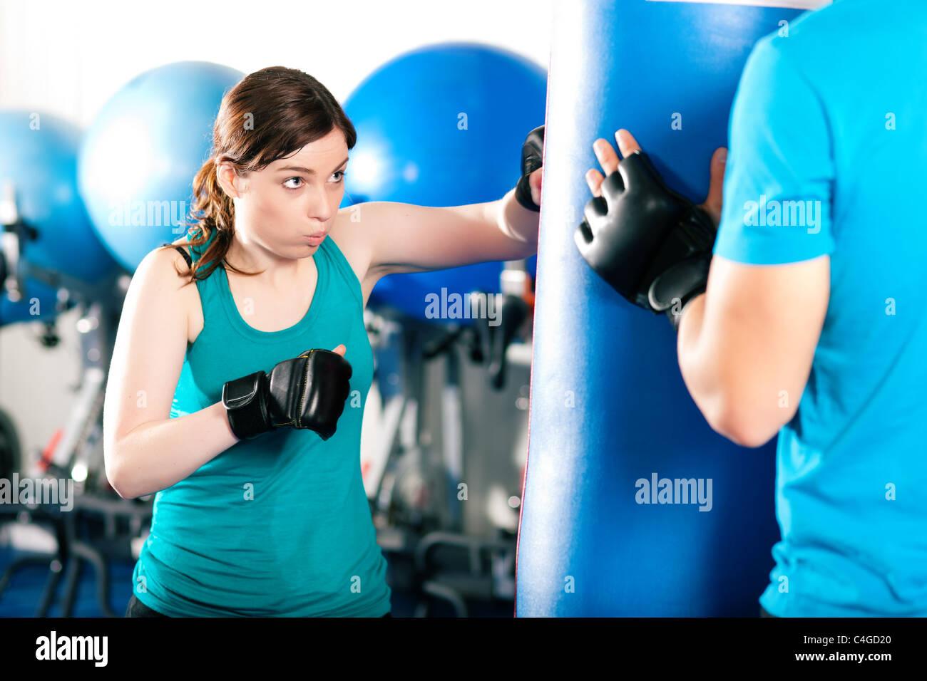 Boxer femme frapper le sac de sable, son entraîneur est d'aider Photo Stock