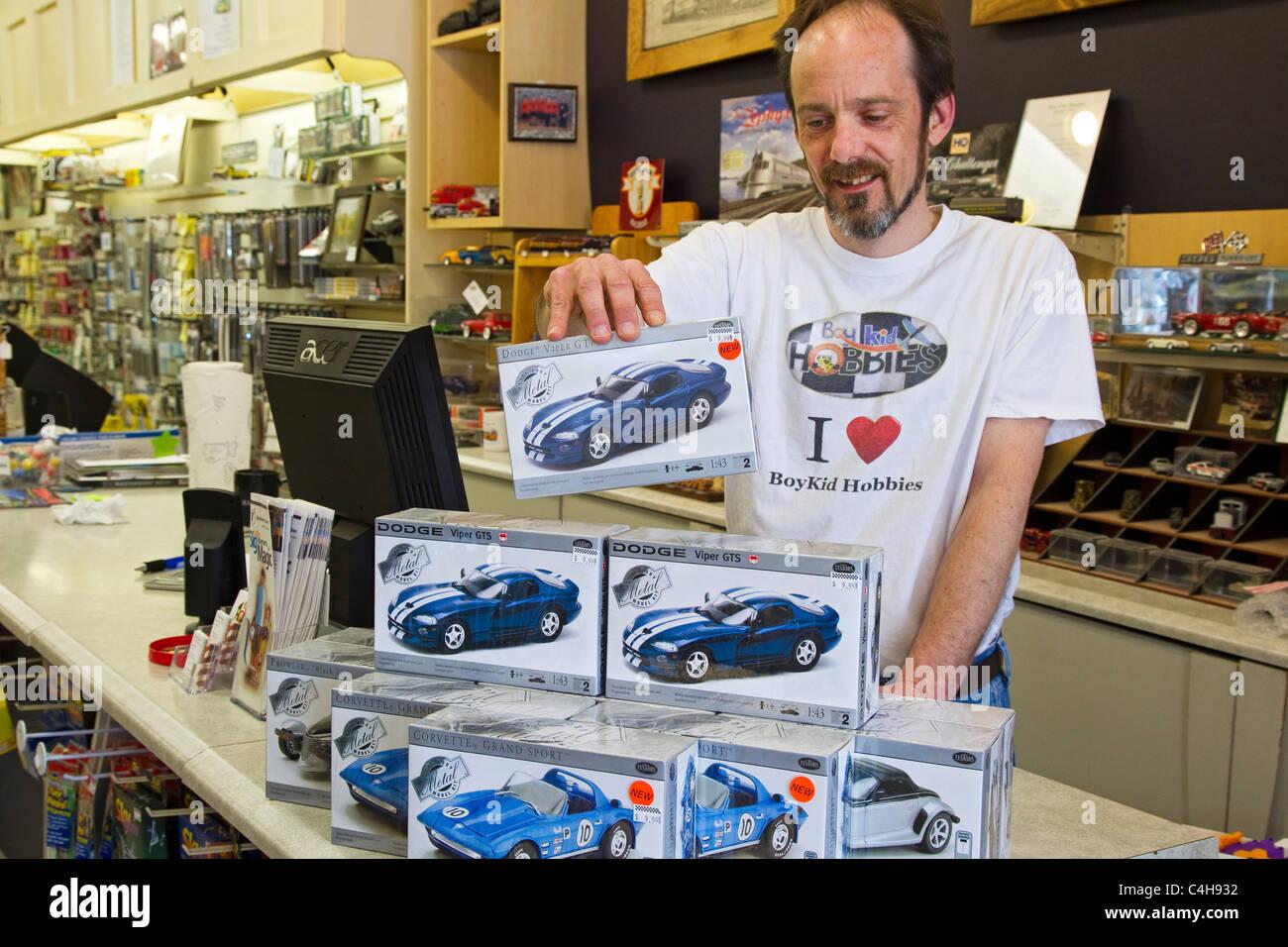 Commis de magasin Hobby voiture modèle empilage des boîtes sur comptoir du magasin Photo Stock