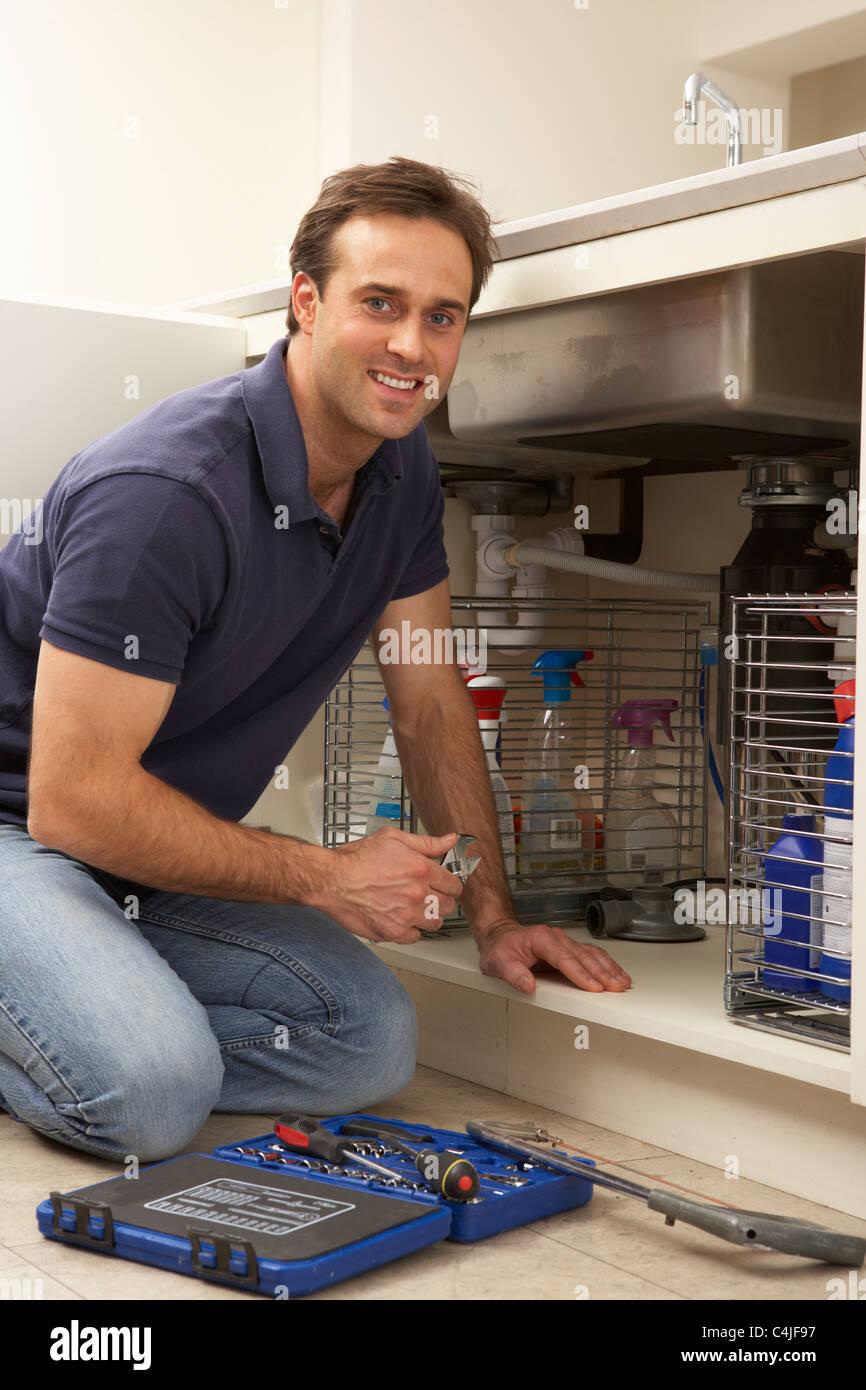 Plombier travaillant sur l'évier dans la cuisine Photo Stock