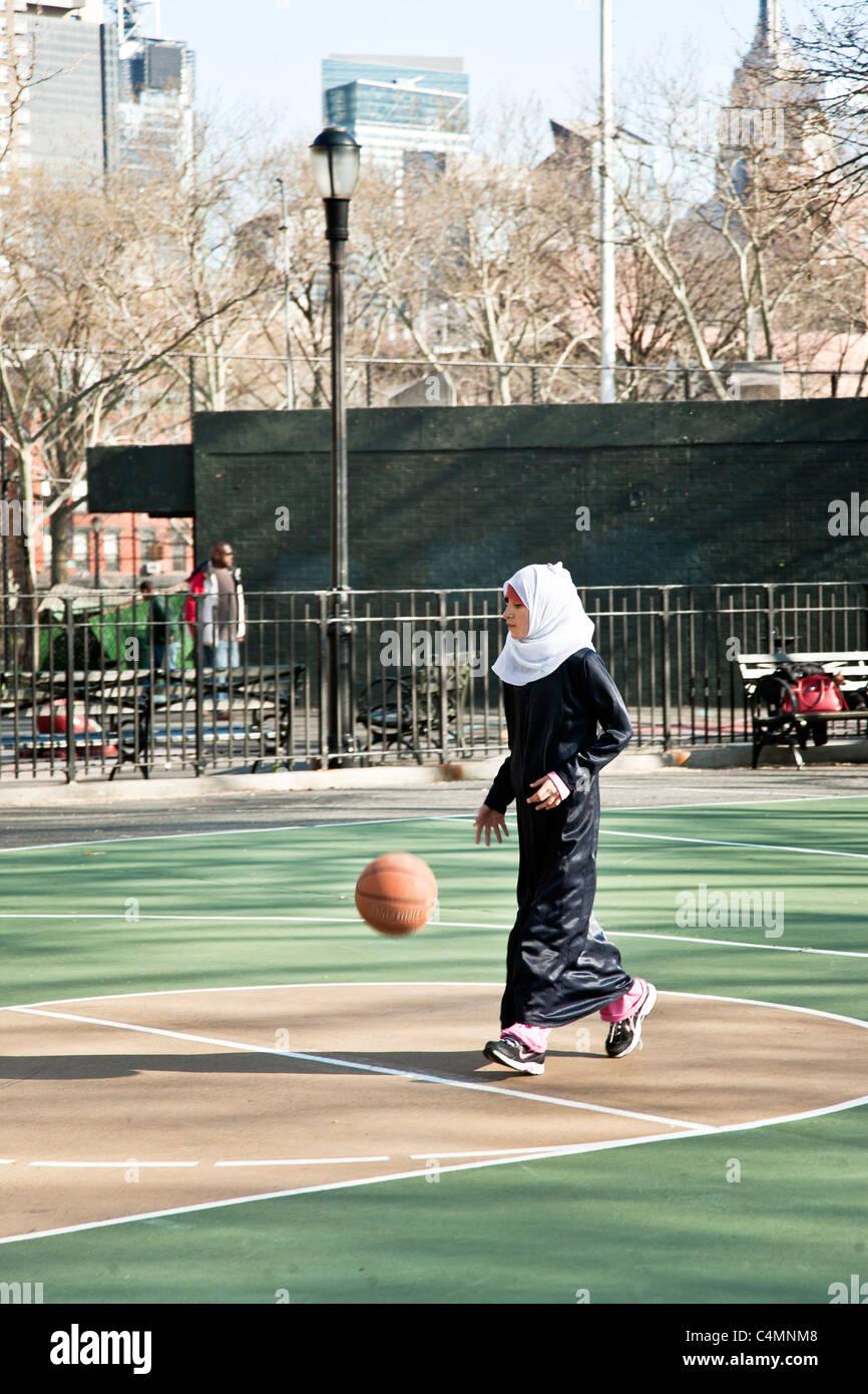 Jolie jeune fille musulmane en foulard abaya noire avec plus de son jean joue avec un ballon de football dans la Banque D'Images
