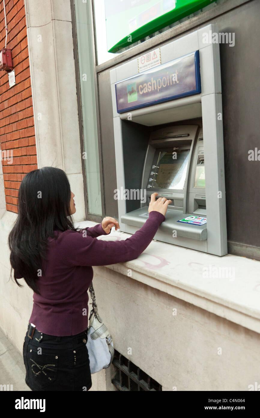 Jeune femme à l'aide d'espèces / ATM machine Banque D'Images