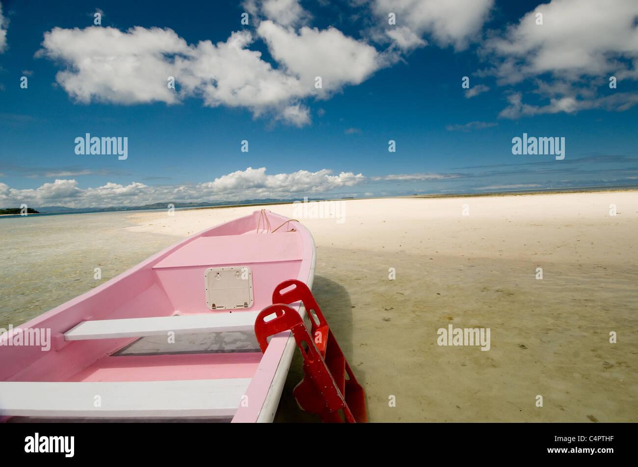Bateau peint rose sur la plage de sable sur la barre de sable island au large de Musket Cove dans le MaloloIsland Photo Stock