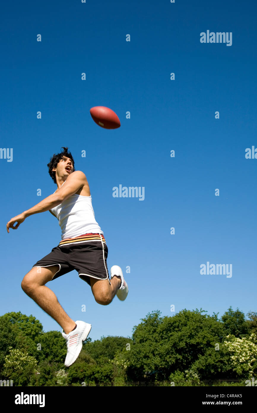 Man jumping jouer avec ballon ovale dans park Photo Stock