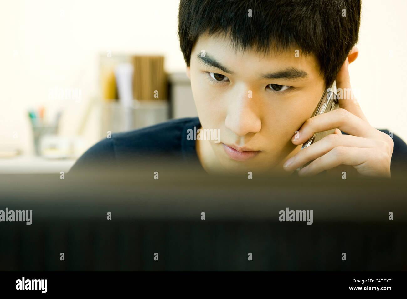 Jeune homme à la recherche à l écran d ordinateur et talking on cell 7768953fa0c7