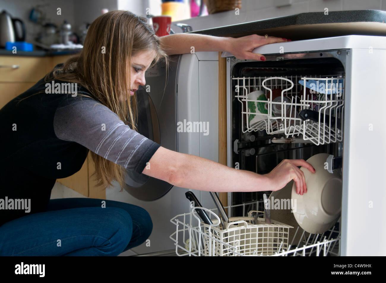 Attractive young woman chargement de la vaisselle sale dans le lave-vaisselle, prises à Bristol, Angleterre, Royaume Banque D'Images