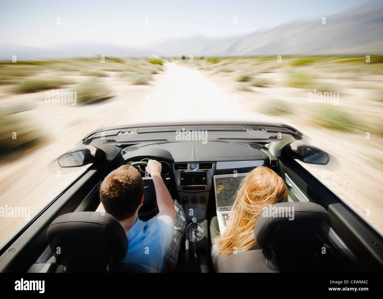 USA, California, Palm Springs, Coachella Valley, San Gorgonio Pass, Couple driving through desert en voiture décapotable Photo Stock