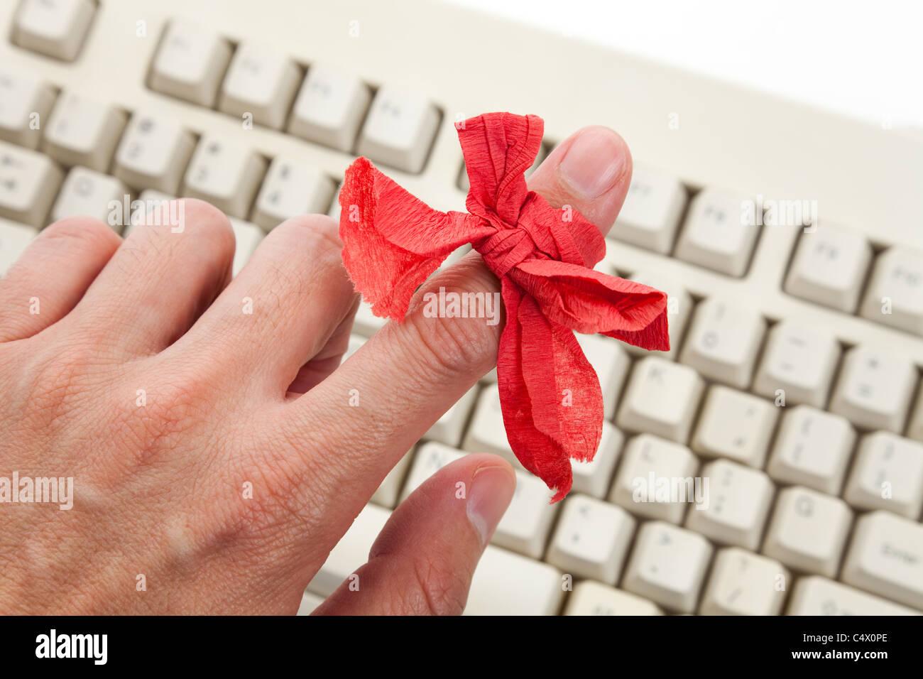 Arc rouge sur le doigt et le clavier de l'ordinateur Photo Stock
