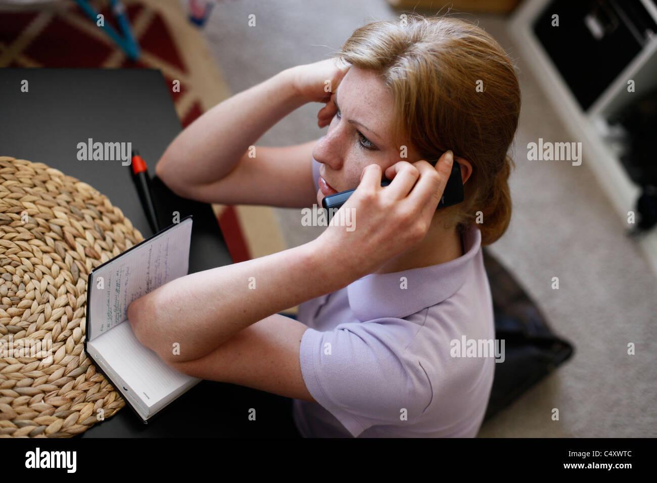 Une jeune femme allemande à l'aide de téléphone fixe à son domicile Photo Stock